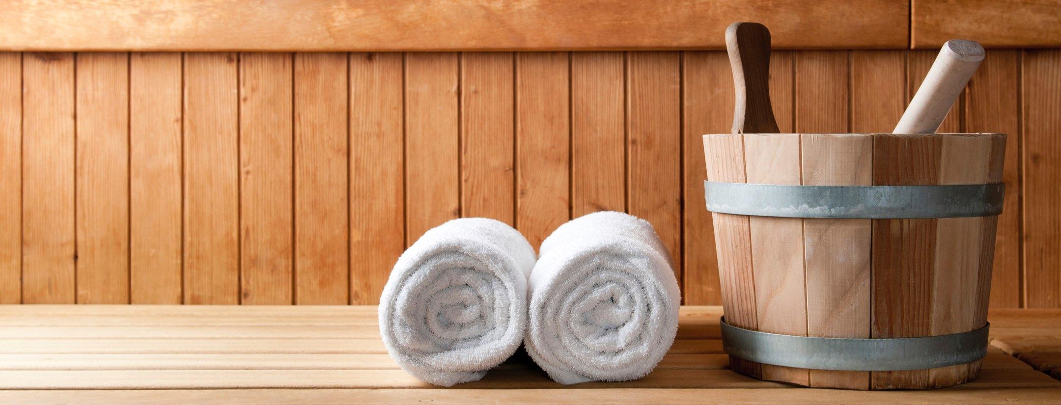 Två handdukar ihoprullade bredvid trähink i bastu