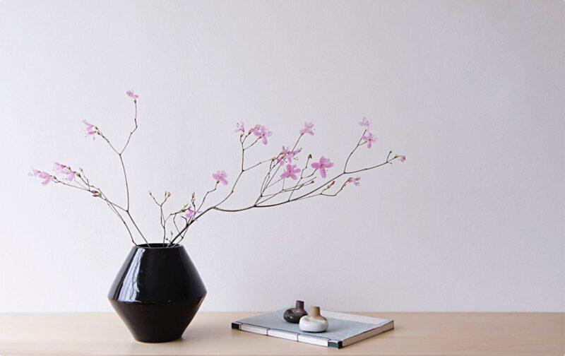 Rosa blommor i en svart vas